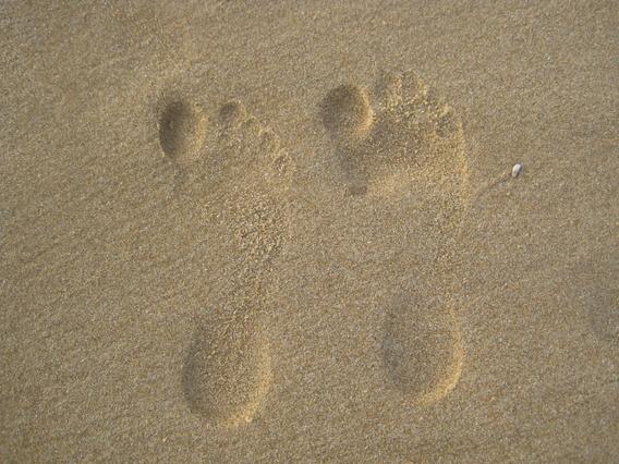 Zwei Abdrücke von Füßen im feuchten Sand