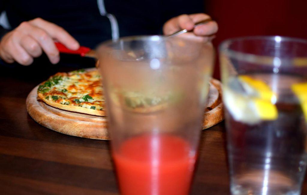Saftfasten, während der Freund Pizza isst